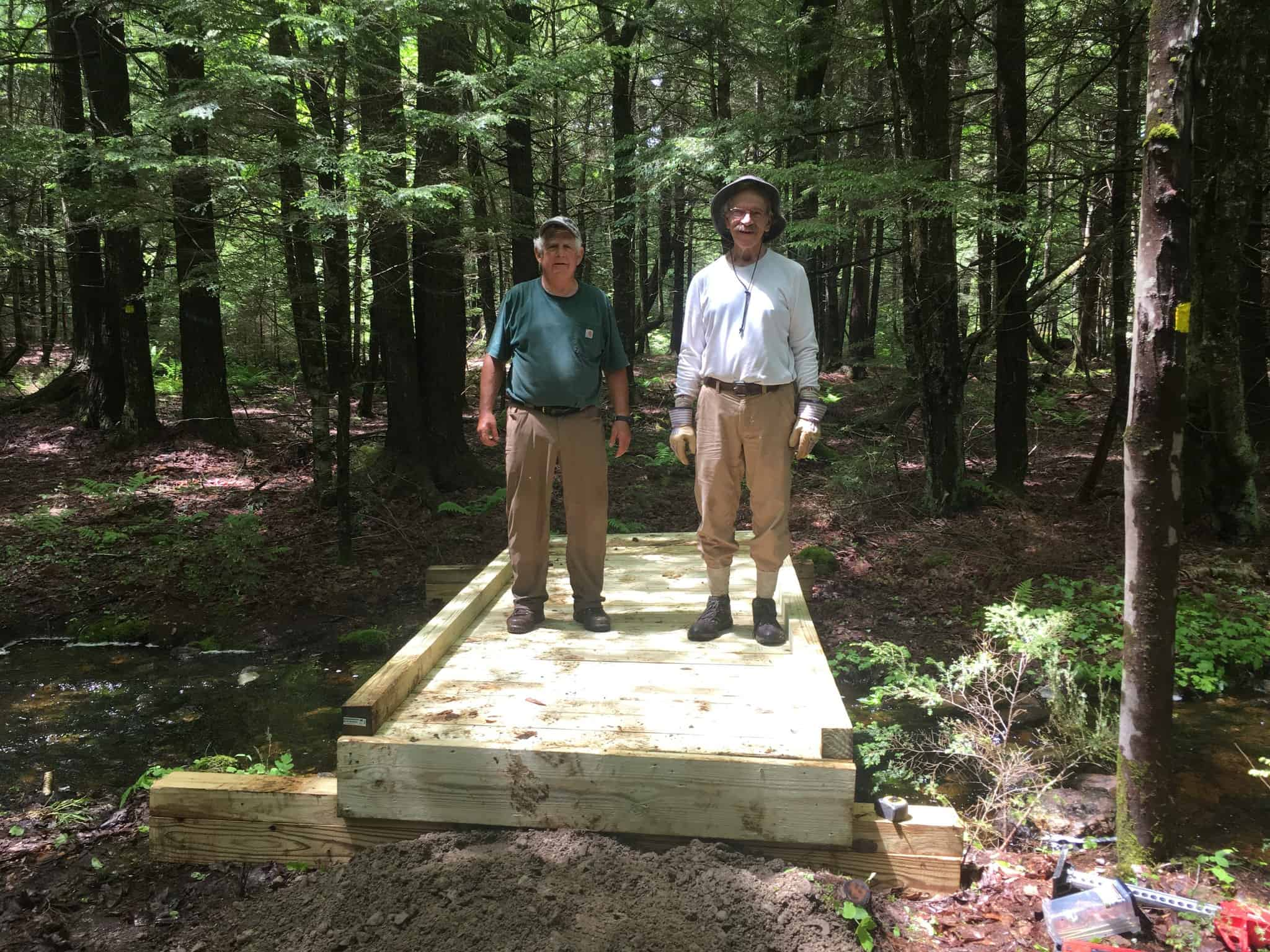 Tom Bratko and Ron Paradise standing on a completed wooden bridge at Rome Conservation Area