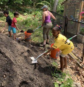 Kids help shovel dirt for a garden